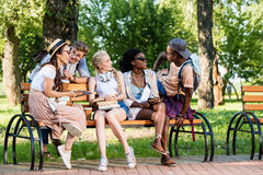 Students resting on bench together in park Royalty Free Stock Photography