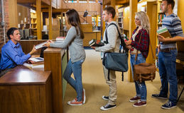 Students in a row at the library counter Royalty Free Stock Photo