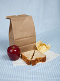 Students Sack Lunch. A students sack lunch with a peanut butter and jelly sandwich, potato chips and an apple Royalty Free Stock Images
