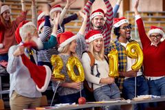 Students in Santa hat holding 2019 golden balloons at New Year party on university royalty free stock photos