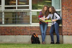Students at school. Two students girls looking at their lessons after school Royalty Free Stock Images