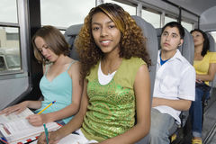 Students In School Bus. High school students doing homework while riding together in school bus Stock Photography