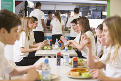 Students in the school cafeteria. High school students eating in the school cafeteria royalty free stock images