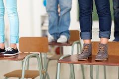 Students school desks. Group of teen students standing on school desks royalty free stock photos