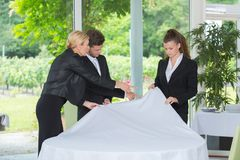 Students setting up tablecloth next to manager. Students setting up a tablecloth next to manager royalty free stock photos