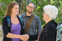 Students Shaking Hands At University Campus Stock Photos