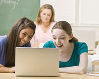Students sharing laptop in classroom Royalty Free Stock Images