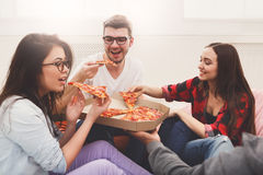 Students sharing pizza at home party. Pizza delivery. Happy people eating lunch at coworking office during break, crop, closeup Royalty Free Stock Image