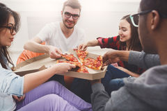 Students sharing pizza at home party. Pizza delivery. Happy people eating lunch at coworking office during break, crop, closeup Royalty Free Stock Photography