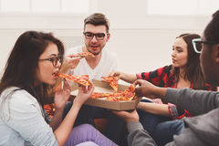 Students sharing pizza at home party. Pizza delivery. Happy people eating lunch at coworking office during break, crop, closeup Stock Photography