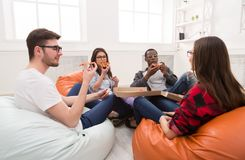 Students sharing pizza at home party. Eating pizza together. Happy people with fast food snack at coworking office during break Stock Image