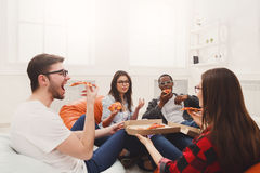 Students sharing pizza at home party. Friends eating pizza. Happy people have lunch at coworking office during break Stock Image