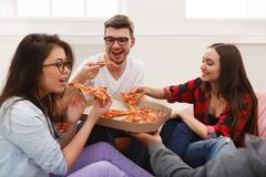 Students sharing pizza at home party. Lunch delivery. Happy people eating pizza at coworking office during break Royalty Free Stock Images