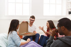 Students sharing pizza at home party Royalty Free Stock Photos
