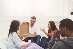Students sharing pizza at home party. Lunch time. Happy multicultural business team eating pizza at modern office during break Royalty Free Stock Image