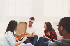 Students sharing pizza at home party. Lunch time. Happy multicultural business team eating pizza at modern office during break Stock Images