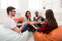 Students sharing pizza at home party. Pizza delivery. Happy people eating lunch at coworking office during break. Fast food snack at work Royalty Free Stock Photo