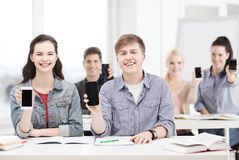 Students showing black blank smartphone screens Stock Photo