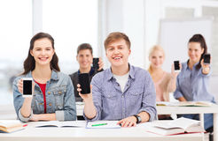 Students showing black blank smartphone screens Royalty Free Stock Image