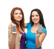 Students showing blank smartphones screens. Education and modern technology concept - smiling students showing blank smartphones screens Stock Image