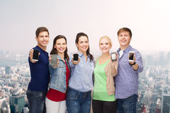 Students showing blank smartphones screens. Education and modern technology concept - smiling students showing blank smartphones screens Royalty Free Stock Images