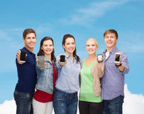Students showing blank smartphones screens. Education and modern technology concept - smiling students showing blank smartphones screens over blue sky background Stock Photos