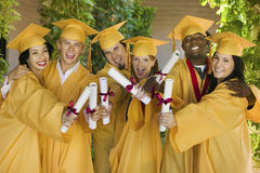 Students Showing Diplomas On Graduation Day In College Stock Photo