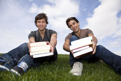Students showing his school books. Two young students giving you books Royalty Free Stock Image