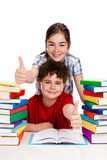 Students showing Ok sign. Students sitting next to piles of books Stock Photo