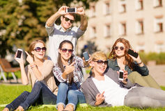 Students showing smartphones. Education, technology, internet, summer holidays, social networking and teenage concept - group of teenagers with smartphones Stock Image
