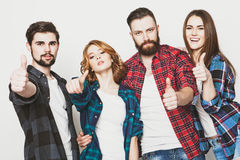 Students showing thumbs up. Life style, education and people concept: happy team of students showing thumbs up. Studio shot over white background. Hipster style royalty free stock image