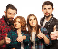 Students showing thumbs up. Life style, education and people concept: happy team of students showing thumbs up. Studio shot over white background. Hipster style stock image
