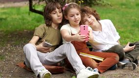 Students sit on the grass during a school break and take a selfie. Two boys and a girl, school friends are photographed. On the camera smartphone. Back to stock video footage