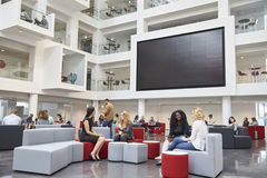 Students sit talking under AV screen in atrium at university Stock Photography