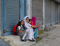 Students sit and wait for the bus to school in Srinagar, India Stock Images