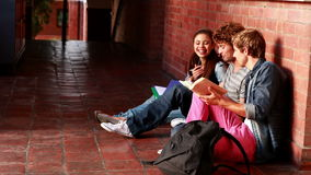 Students sitting against wall revising together Royalty Free Stock Photo