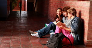Students sitting against wall revising together Royalty Free Stock Images
