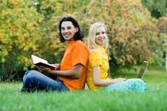 Students sitting back to back. Students studying together, on grass Stock Photos