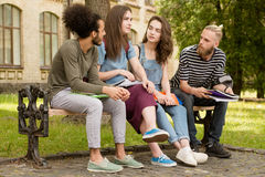 Students sitting on bench telling stories. Stock Photography