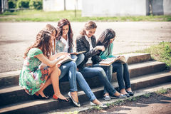 Students sitting with a books on street Royalty Free Stock Photos