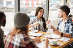 Students sitting during coffee break in the cafe. Tea time. Happy smiling asian girl having nice conversation with her male friend while drinking tea at cafe Stock Photo