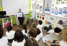 Students sitting on the floor listening to the story Royalty Free Stock Photography