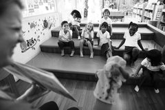 Students sitting on the floor listening to story te Royalty Free Stock Photo