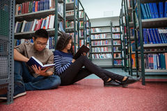 Students sitting on the floor and reading books Royalty Free Stock Photos