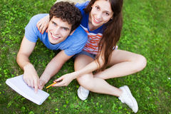 Students sitting on grass Stock Images