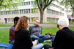 Students sitting on grass visiting Royalty Free Stock Photo
