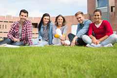 Students sitting in the lawn against college building Stock Photo