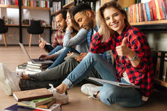 Students sitting in library on floor showing thumbs up. Stock Images