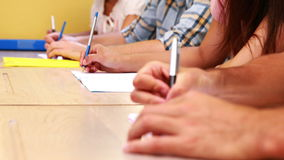 Students sitting in a line taking notes in classroom Stock Photo