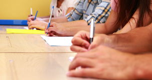 Students sitting in a line taking notes in classroom Royalty Free Stock Photos